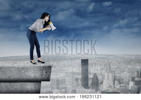 Picture of young businesswoman shouting by using a megaphone while standing on the stone