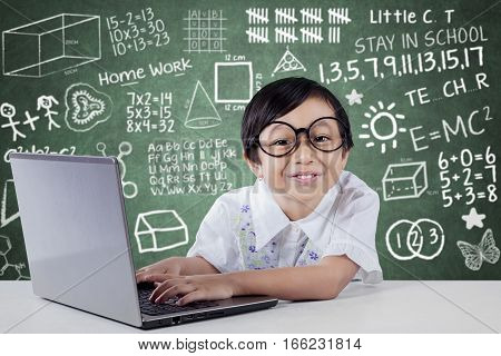 Cute little student using laptop computer while smiling at camera with scribble background on the blackboard