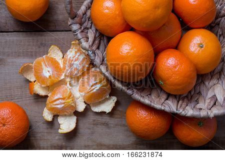 Many ripe mandarins in a basket. One peeled and divided into lobules. Several pcs lie on a wooden table. top view