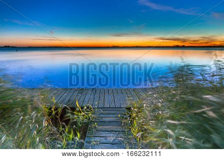Long Exposure Image Of Blue  Sunset Over A Jetty On The Shore Of A Lake