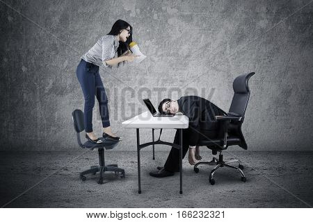 Picture of female entrepreneur shouting to her tired employee with a megaphone while standing on the chair