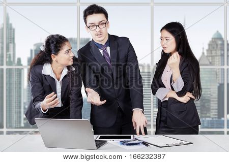 Group of three young entrepreneurs standing in the office while debating and discussing in a business meeting