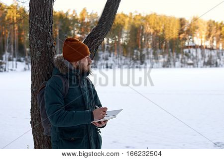 Researcher take notes in notebook outdoor in sunny winter day. Tourism concept with tourist in green jacket red hat who writing in book nature landscape.