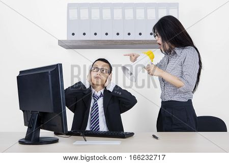 Young female employee is screaming at her manager through megaphone while working with a computer in the office room
