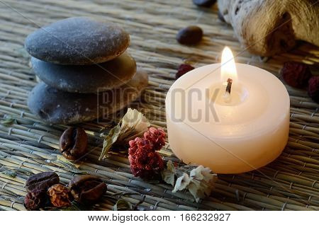 Spa still life - massage stones,candle and body scrub components (coffee beanssaltdried hawthorn berries and lavender leaves )