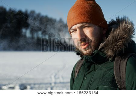 Man exhale smoke after smoking outdoor in winter day with countryside background. Close up portrait of looking to the camera smoker in green jacket and red hat.