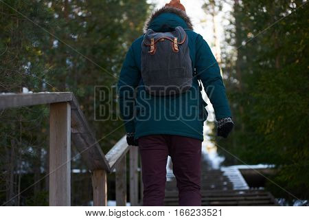 Back view on man who climb up the stairs in mountain region. Ecological tourism by foot in winter sunny day.
