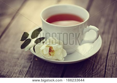 White cup on a wooden table and a branch of the white wild rose