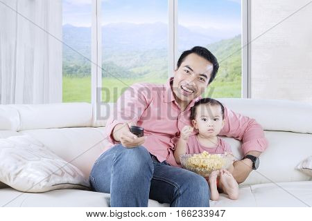 Portrait of little daughter eating popcorn on bowl while watching tv with her father