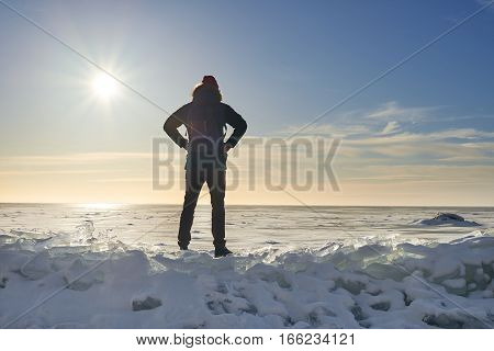 Man stay on the finish ad look to the horizont. Travel concept in winter time. Sunny day with blue sky and frozen sea. Cosmic landscape. Feel freedom. Open space.