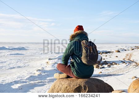 Meditation concept. Man have relax after hard jorney. Guy look far to the horizon. Open space. Free place for advertising travel goods or tourism stuff. Winter landscape with frozen sea.