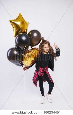 Little modern hipster girl in fashion clothes hold baloons and make peace by her hand. Studio