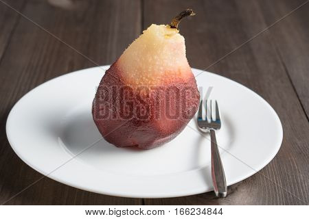 one poached pear on white plate with fork on dark wooden background