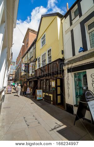 EXETER DEVON UK 22 July 2016: Narrow street. City center. Two pedestrians walk. Colored houses.