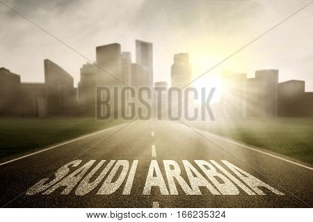 Highway towards to a town and sunrise with Saudi Arabia word