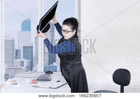 Stressful woman throwing her computer with financial crisis chart on the desk in office