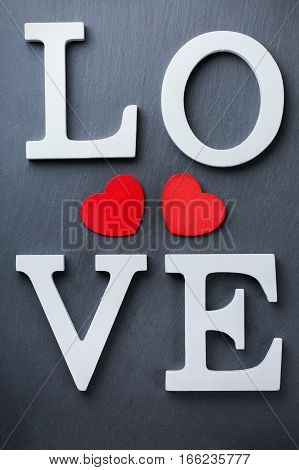 Love and still life concept. Valentines day holiday letters text message card with red hearts. Top view flat lay overhead