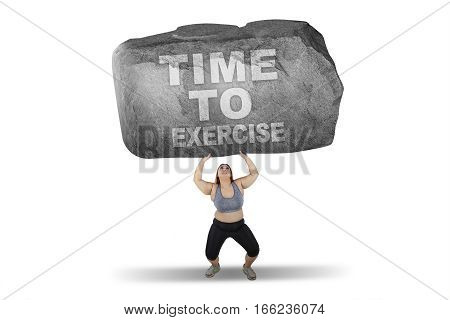 Obese woman lifting big stone with time to exercise word isolated on white background