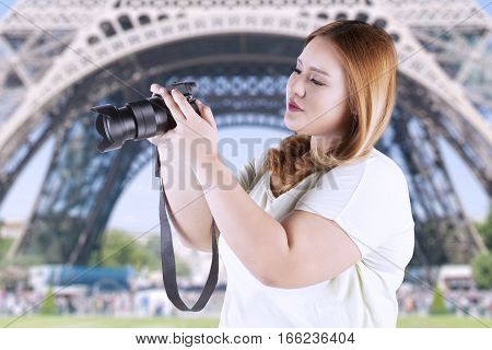 Portrait of blonde hair woman taking picture by using digital camera while standing in front of eiffel tower