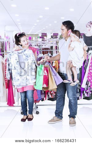 Full length of beautiful woman trying new clothes with her family while standing in fashion store