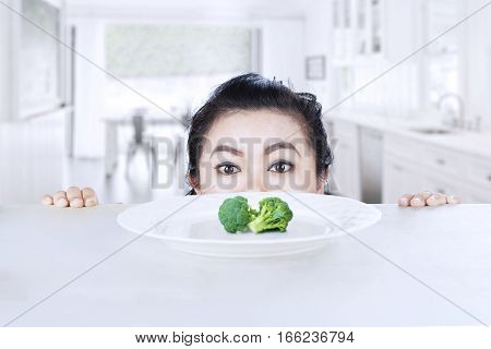 Picture of young woman peeping broccoli on a plate in the kitchen