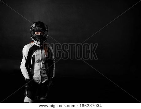 Young handsome woman model in motorcycle concept. Extreme girl in bike helmet and motor protection race suit on black background with free space for advertising or goods.