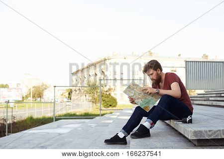 Handsome man read the map of european city on stone steps. Tourism or urban explore concept. Hipster bearded guy in red t shirt dark blue jeans white socks and black boots.