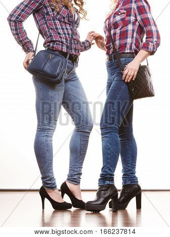 Generation and fashion concept. Adult daughter and mother posing with handbags. Two casual style women wearing denim pants plaid shirts