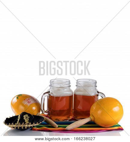 Cinco de Mayo concept with freshly poured beer maracas sombrero and placemat serapes on glass table isolated on white.