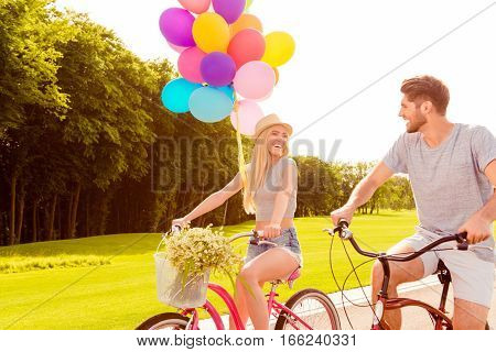 Happy Smiling Cheerful Couple With Balloons Riding Bikes