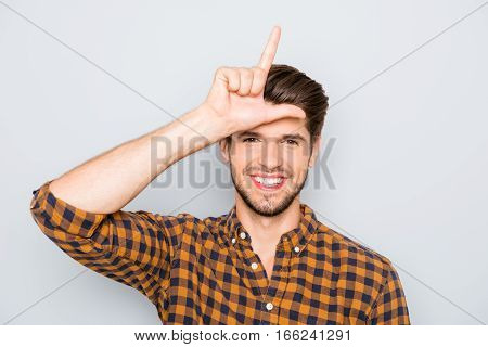 Funny Young Man Showing Sign Of Loser With Fingers Near Head