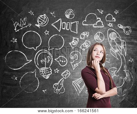Portrait of a girl with braided hair wearing a red dress who is standing near a blackboard with start up icons drawn on it.