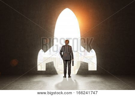 Rear view of a man holding a suitcase and standing near a rocket opening in a black wall. Toned image. Mock up