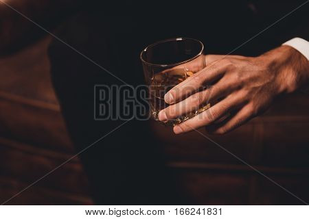 Close Up Of Man's Hand Holding Class Of Whiskey