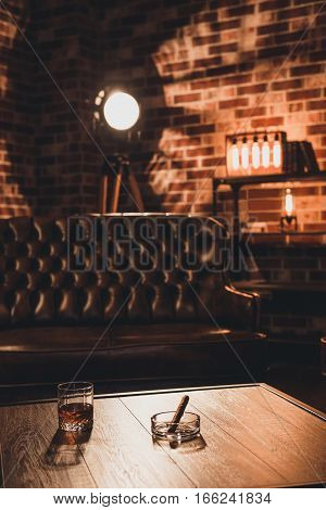 Loft Interior. Leather Couch With Glass Of Whiskey And Cigar On Table