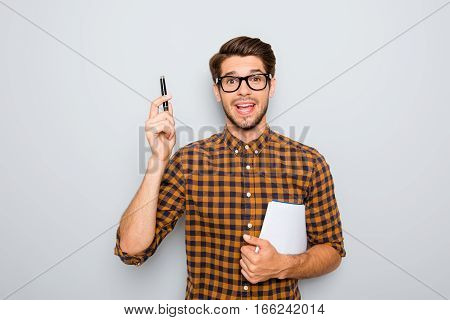 Smart  Student In Glasses  With Great Idea Holding Notebook And Pen