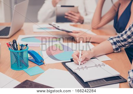 Close up of woman making notes on business meeting