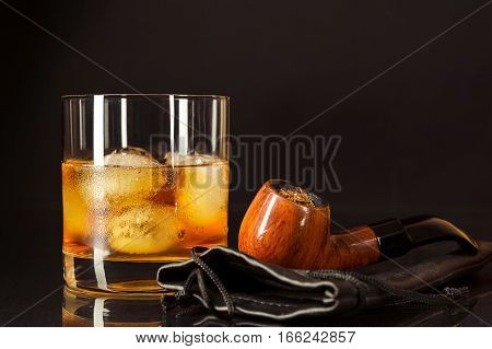 Scotch drink glass and smoking pipe on black background. Whiskey or Brandy glassful as unhealthy Still Life concept. Bad Habits symbol.