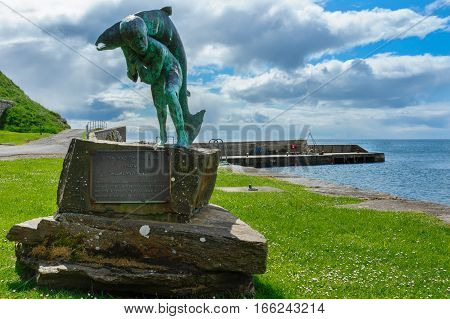 Dunbeath Scotland - June 4 2012: Kenn and the Salmon statue stands in the harbor. Green meadow part of the harbor pier blue sky with large clouds. Scene out of Highland River book written by Neil Gunn.