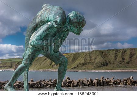 Dunbeath Scotland - June 4 2012: Closeup of Kenn and the Salmon statue which stands in the harbor. Green cliffs and North Sea in background. Dark cloudy sky with blue patch. Scene out of Highland River book written by Neil Gunn.