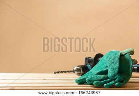 Green working gloves with green drill on lining wooden table with copy space.
