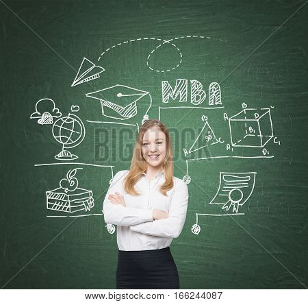 Portrait of a smiling blond woman standing with crossed arms near a green chalkboard with MBA sketch on it.