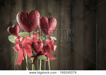 Flower in the shape of heart made from foam borad on brown wood background vintage and dark tone with valentines day background concept