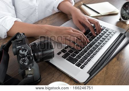 Photographer editing photos on laptop. Studio work, photo service concept. Workplace