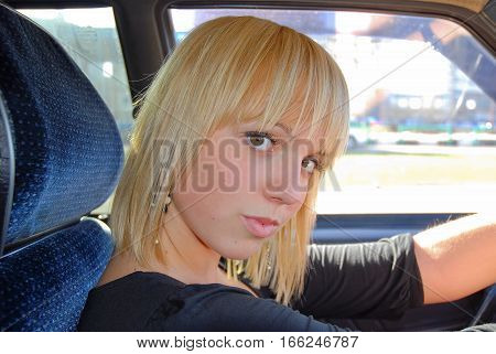 Blonde girl is sitting behind the wheel of a car