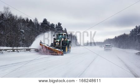Tractor deicing and cleaning a asphalt highway in winter.