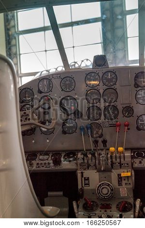 Airplane cockpit control panel with various buttons levers displays and knobs