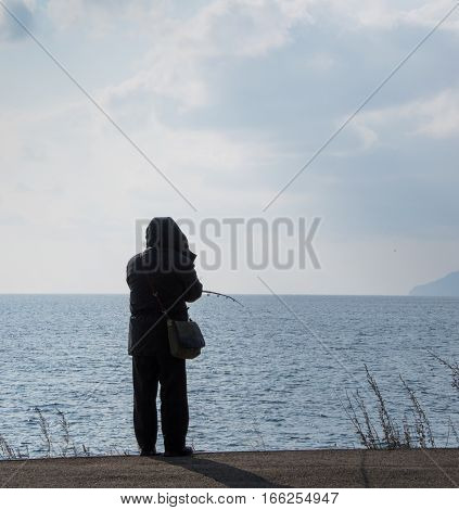 Fisherman dressed in black, with his back to the camera, fishing from the bank of Lake Baikal in Siberia. The water is choppy and a  gray blue.
