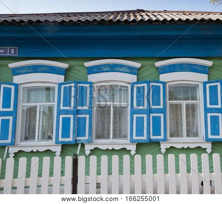 Three windows in a green house with white and blue trim and panels white and blue shutters. A white picket fence is in the foreground. Lace curtains hang in the windows. Photographed in Listvyanka Siberia.