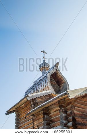 An old Russian Orthodox church constructed with logs in Taltsy Museum, Siberia. The intricate shingles with a unique shape on the roof and onion dome as well as the cross are also made of wood.